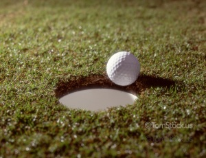 Golf ball at edge of hole